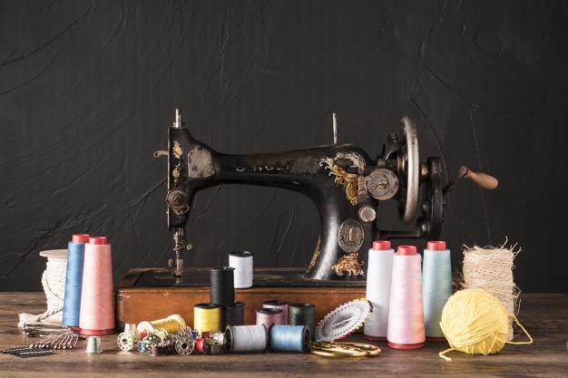 Different essential sewing tools around vintage machine