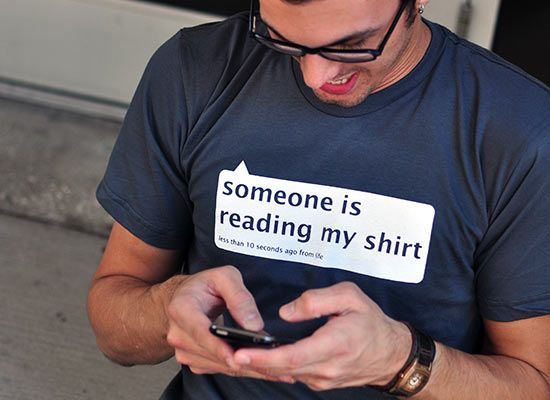 Man in T-shirt with a funny message texting on the smartphone