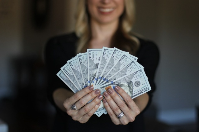 Pile of money in the woman's hand