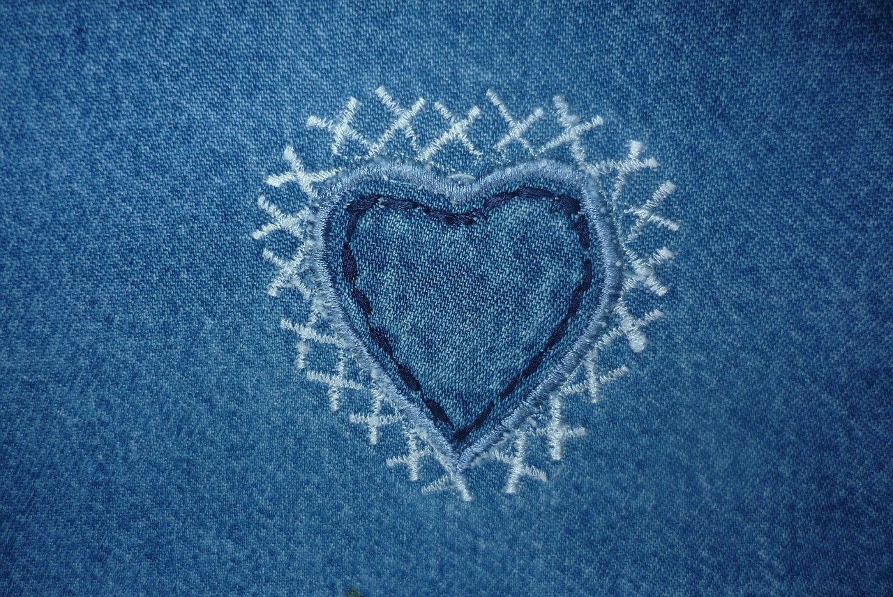 Sewing in the form of heart on denim.
