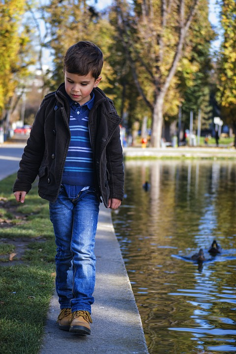 Toddler walking by the water in denim jeans - the most durable fabric for children's clothes