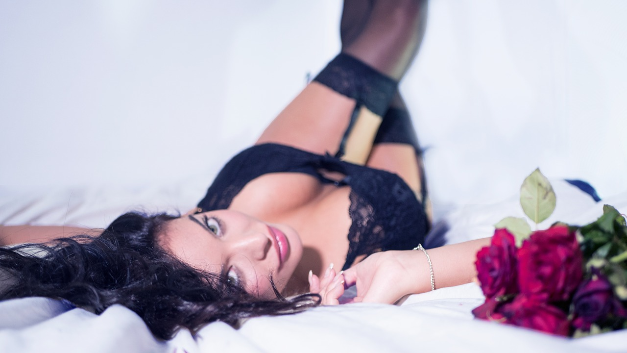 Woman laying in bed in laced lingerie