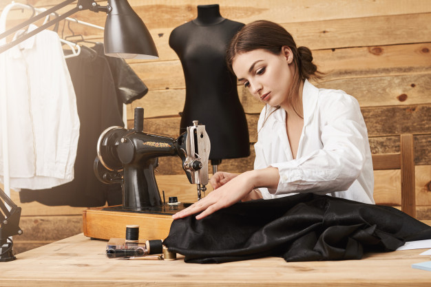 Woman sewing on sewing machine without the finger's protection which isn't secure