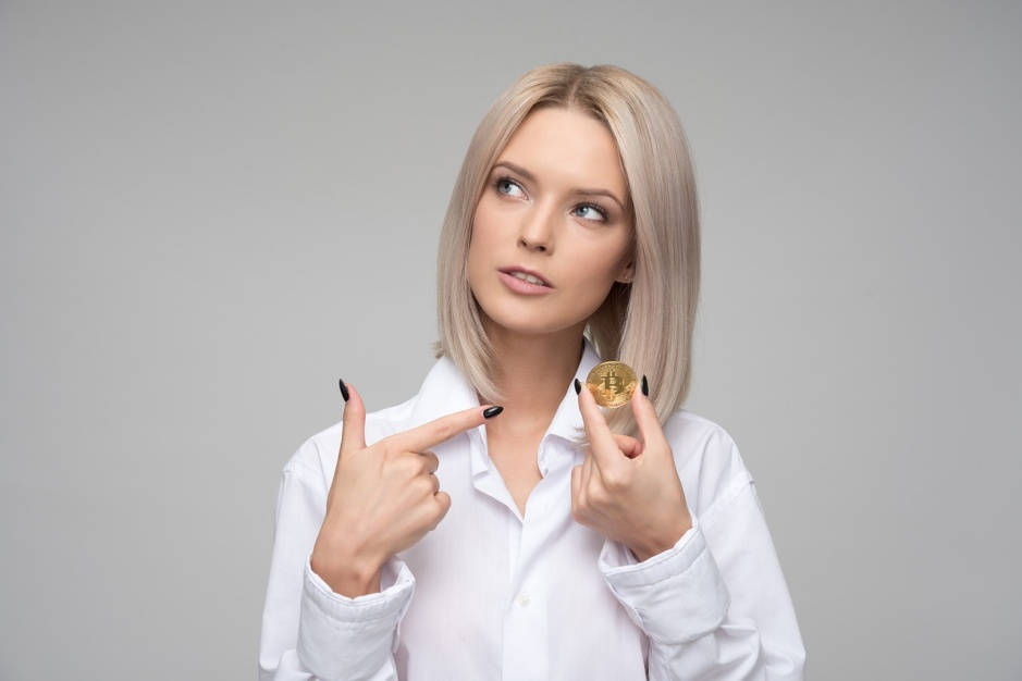 Woman thinking about the money value while pointing on a coin in her hand
