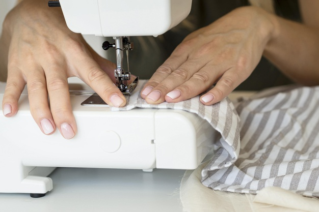 Women is sewing bare-handed - not a secure way of using sewing machines