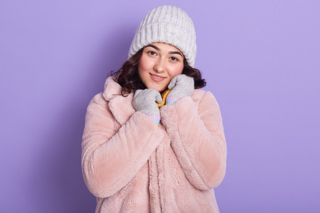 Young woman dressed in pink coat made from faux fur